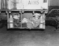 Two boys with milk canisters in a cargo bay of a truck Royalty Free Stock Photo