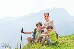 Two boys with mother are sitting on a top of mountain Royalty Free Stock Photo