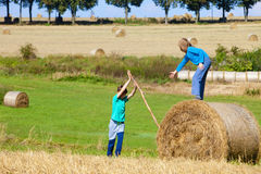 Two Boys Moving Bale of Hay Stock Photo
