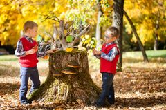 Two boys in the autumn park. Two boys near the magic stump with gingerbread in the autumn park Royalty Free Stock Photo