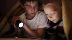 Two  boys at night under a blanket reading a book. Two boys at night under a blanket reading a book with a flashlight stock video footage