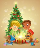 Christmas miracle - boys opening a magic gift beside a Christmas tree stock illustration