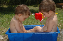 Two boys outside in bath tub. Two boys playing with water in big plastic tub outdoors Stock Photos