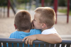 Two boys outside sharing a secret Royalty Free Stock Image