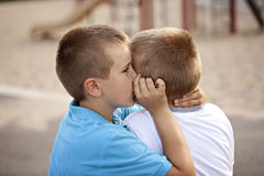 Two boys outside sharing a secret Stock Image