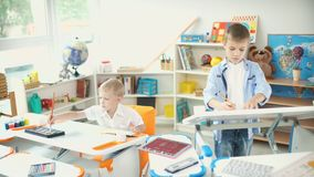 Two boys painting in a beautiful nursery stock footage