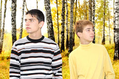Two boys in the park. Two teenage boys in the autumn park look in different directions Stock Photo