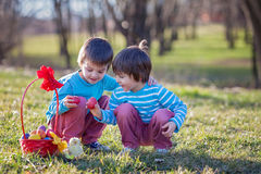 Two boys in the park, having fun with colored eggs for Easter Royalty Free Stock Images