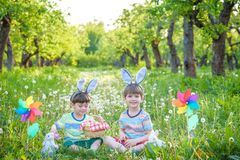 Two boys in the park, having fun with colored eggs for Easter stock photography