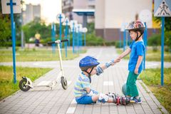 Two boys in park, help boy with roller skates to stand up. Two boys sibling brothers together in park, helps boy with roller skates to stand up after fall stock images