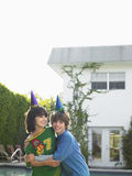 Two boys In Party Hats Playing In Front Of House Royalty Free Stock Images