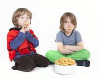 Two boys with peanut puffs Royalty Free Stock Photography