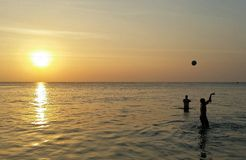 Two boys plaing ball on the sea Stock Image