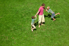 Two boys play with the adult a lawn. The top view. stock photos