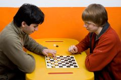 Two boys play checkers Stock Image