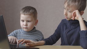 The two boys play in a computer game online stock footage