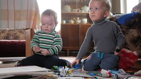 Two boys play at home with stationery. Cute brothers spend interesting time stock footage