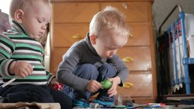 Two boys play at home with stationery. Cute brothers spend interesting time.  stock video