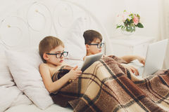 Two boys play at laptop and tablet with dog in bed Stock Photo