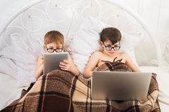 Two boys play at laptop and tablet with dog in bed Stock Photos