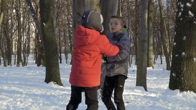 Two boys play snowballs in winter forest, slow motion. Three brothers play snowballs at winter park. Boys hide behind the trees and throws snowballs in each stock video