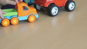 Two boys play toy model cars at the table stock video footage