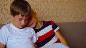 Two boys play on a white  plate sitting on the stock video footage
