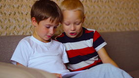 Two boys play on a white plate sitting  on the. Two boys play on a white plate sitting on the couch stock footage