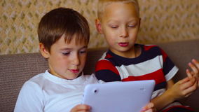 Two boys play on a white plate sitting on  the. Two boys play on a white plate sitting on the couch stock video footage