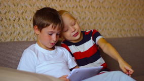 Two boys play on a white plate sitting on the. Couch stock video footage
