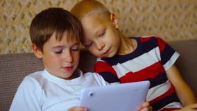 Two boys  play on a  white plate  sitting on the. Two boys play on a white plate sitting on the couch stock video