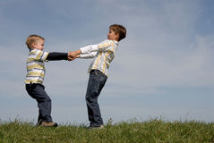 Two boys playing. Brothers having fun on top of a hill Stock Photo