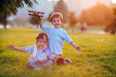 Two boys, playing with airplane on sunset in the park Stock Image