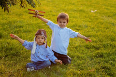 Two boys, playing with airplane on sunset in the park Royalty Free Stock Images