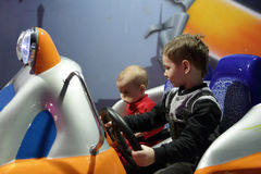 Two boys playing arcade game machine. At an amusement park Royalty Free Stock Photo