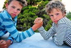 Two boys playing armwrestling outdoors stock images