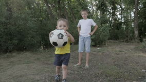 Two boys playing with a ball. In the park stock footage