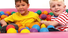 Two boys playing in a ball pit. In slow motion stock video