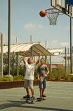 Two boys playing basketball  . Two boys playing basketball standing on a skateboard in a sunny summer morning Royalty Free Stock Images