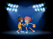 Two boys playing basketball at the center of the stage Stock Images