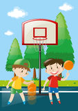 Two boys playing basketball in court Stock Photography