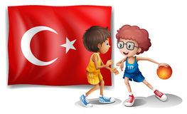 Two boys playing basketball in front of the flag of Turkey Royalty Free Stock Photos