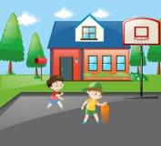 Two boys playing basketball at home Stock Photo