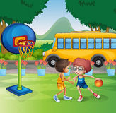 Two boys playing basketball near the school bus Stock Photos