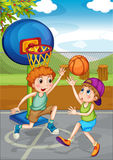Two boys playing basketball outside Stock Photography