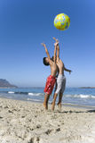Two boys playing with beach ball on beach near ocean Stock Photo