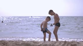 Two boys are playing on the beach stock footage