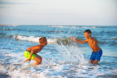 Two boys playing at the beach with water. Royalty Free Stock Photography
