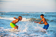 Two boys playing at the beach with water Royalty Free Stock Images