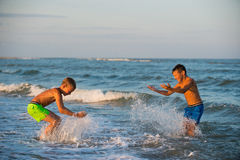 Two boys playing at the beach with water. Stock Image